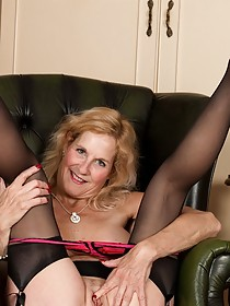Stockings-clad MILF shows her wrinkly pussy on a leather chair