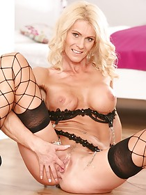Fishnets-wearing blonde beauty fingering her awesome pussy on the floor