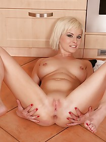 Short-haired blonde sucking on her fingers and masturbating in the kitchen
