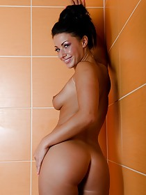 Stacked brunette with a great tan fingering her juicy little pussy